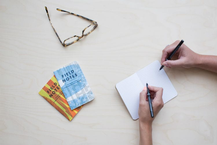 handen met pen en bril
