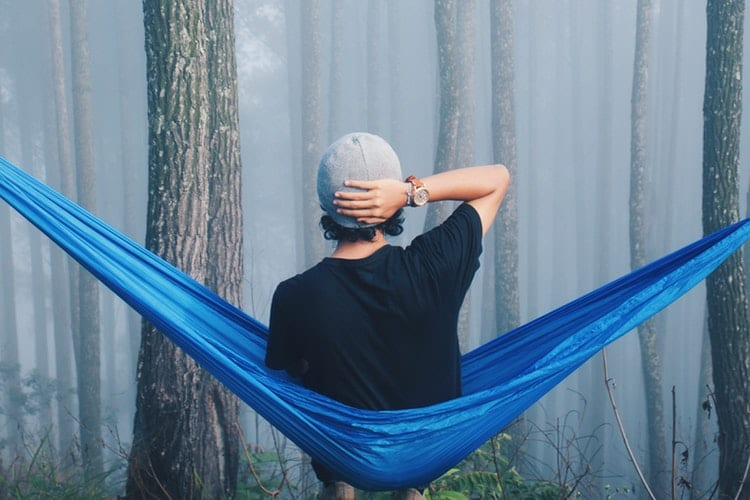 4 tips om uit de ratrace te stappen-by Ibadah Mimpi- person-sitting-on-blue-hammock-surrounded-with-tall-trees-3230849