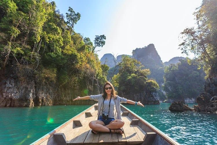 werk tijdens vakantie - Zo krijg je jouw werk af én vier je vakantie - by Te LensFix - photo-of-woman-sitting-on-boat-spreading-her-arms-1371360