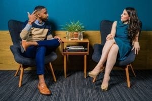 Discussie - Van irritante discussie naar waardevol gesprek- by Jopwell - woman-wearing-teal-dress-sitting-on-chair-talking-to-man-2422280