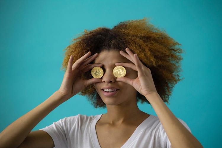 Ook jij kan miljonair en financieel onafhankelijkworden. Young professiona houdt gouden munten voor haar ogen