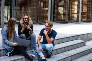 Hoe functioneer jij in een team - sollicitatieserie - by Buro Millennial - three-persons-sitting-on-the-stairs-talking-with-each-other-1438072